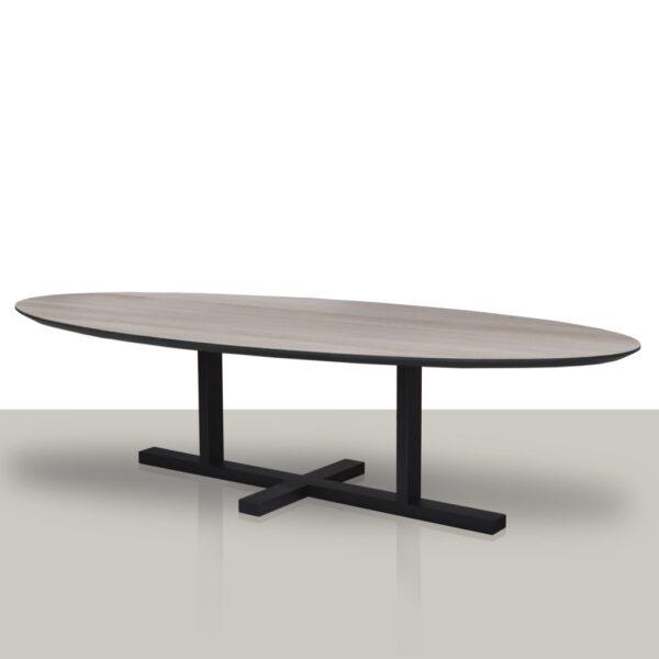 Ovale eettafel met een metalen H onderstel en een eikenhouten tafelblad met zwarte rand.